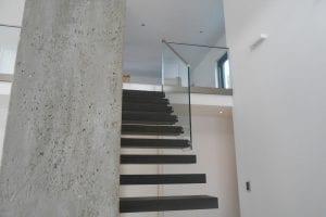loft-treppe-mit-glasgelaender-neben-betonsaeule